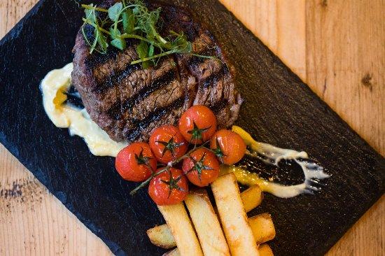 Tron Bar & Kitchen: 28 day aged ribeye of Blackgate beef skin on rooster chips vine tomatoes aioli, credit John John