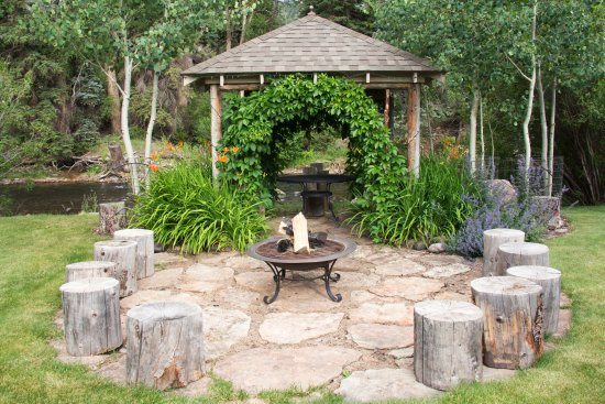 South Fork, CO: Stone fire pit with log seating and riverfront arbor