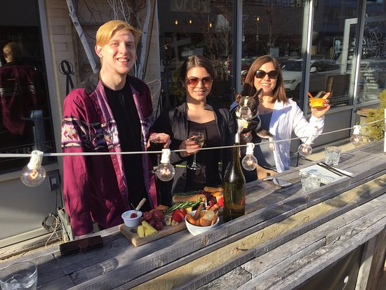 """Asbury Park, Nueva Jersey: Kyle Graef, Emily and Kimberly Greenheim and dog """"Ozzy"""" enjoying a warm afternoon at Lola's Cafe"""