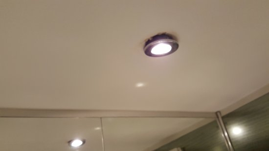 Bathroom Lights Edinburgh light fixture partially hanging from ceiling in bathroom