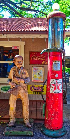 Koloa, HI: Wood carving and old gas pump.