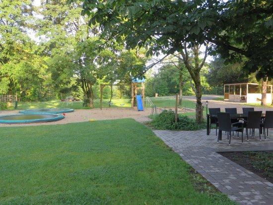 Hejnsvig, Danmark: Legeplads med boldbanen bagved og hus med bordtennis
