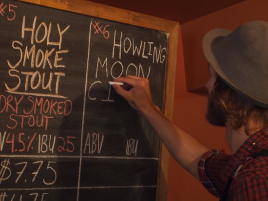 Oliver, Canada: Sid writing on our chalkboard. As well as our beer we have cider, wine and non-alc beverages