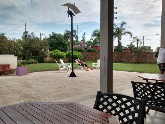 Ramallo, Argentina: Pequeño parque VERDE, desde una galería bajo techo con mesas.