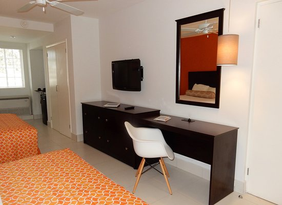 Talk of the Town Hotel & Beach Club: Desk, dresser, TV and charging station at Superior room.
