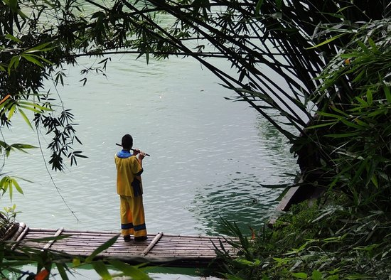 Yichang, China: Costumed man playing a flute on a raft by the river