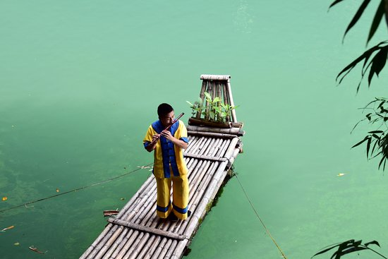Yichang, China: Costumed flautist on the river tributary