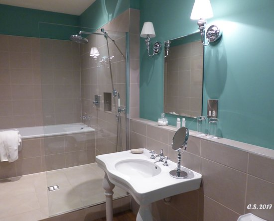 A raised shower area with a fixed shower head and a hand held shower ...