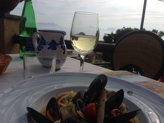 Rosiello: Spaghetti con frutti di mare acompañado con un vino blanco de la casa. De fondo, la increíble vi