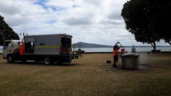 Auckland Domain: Worker cleaning up the electric barbecue pit .