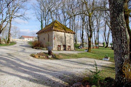 Payrac, France: les parkings et la petite maison qui sert de rangement pour le bois