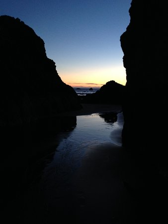 Port Orford, OR: sunset peeking through the beach rocks