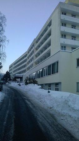 Jachymov, Tjekkiet: Hotel ze strany od kopce s hlavním vchodem a parkovištěm