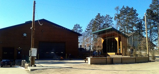 Nisswa, MN: The back of Gull Dam Brewing building with patio fire pit and stage.