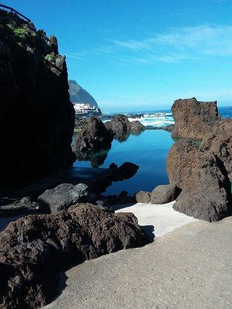 Porto Moniz Natural Swimming Pools: Trotz wildem Meer spiegelglatte Wasserfläche. Im Hintergrund sieht man ein Restaurant