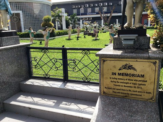 Palo, Filippijnen: I parken intill kyrkan ligger massgraven efter tyfonen Yolanda.