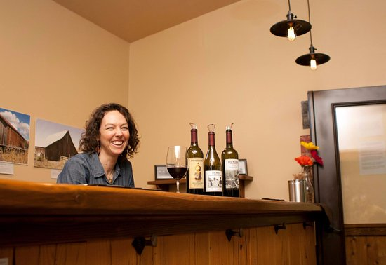 Dayton, WA: One of the owners, Ali, pouring wine in their tasting room
