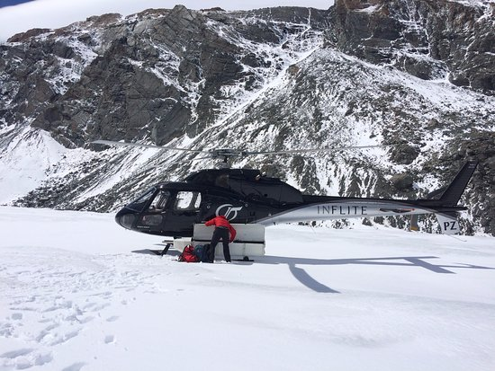Aoraki Mount Cook National Park (Te Wahipounamu), Yeni Zelanda: The helicopter has landed on Mount Cook Glacier and the guide is getting the gear to start the h