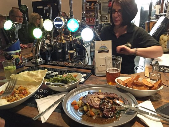 Bridgwater, UK: The £5 menu (plus some extra chips and veg) - rump of lamb and a curry. Rachel in the background