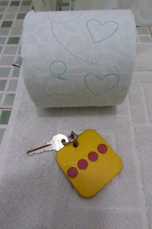 Hotel Maria Guadalupe: Toilet paper with green hearts, and four-dot room key, on bathmat