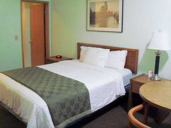 Travelodge Seattle North of Downtown: Bathroom door in distance.  Decent size, and two chairs at table.  Microwave and fridge.
