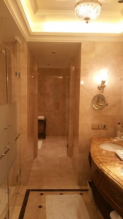 """The Leela Palace New Delhi: """"Pullman"""" type bathroom with vanity on the right, shower/toilet on the left. Tub room at the end"""