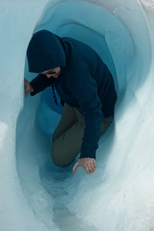 Fox Glacier Guiding: crawling through an ice tunnel!