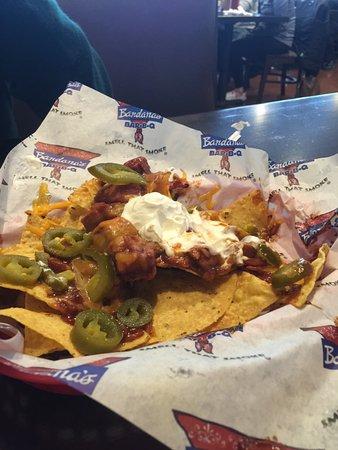 Cedar Rapids, Iowa: I admit we had eaten some of the nachos B4 the photo. BBQ chicken, cheese, sour cream, peppers