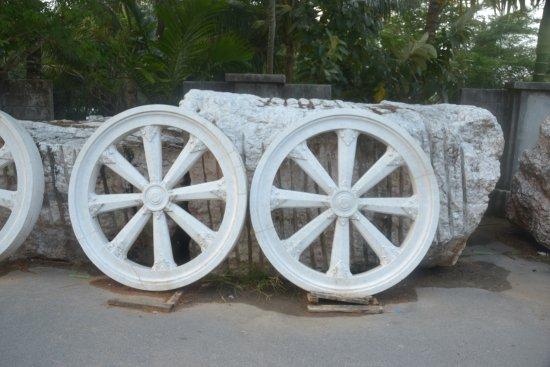 Chalong, Tailandia: У постамента статуи разбросано множество колес из мрамора в рост человека.