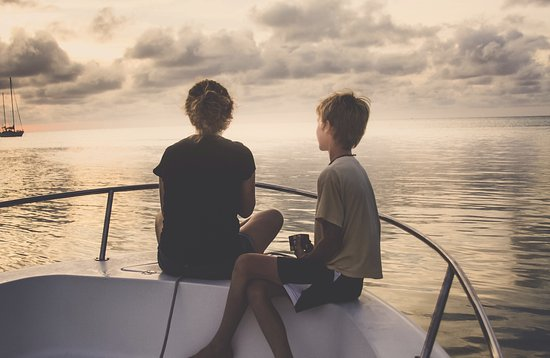 "Folly Beach, Южная Каролина: Two teens aboard Sail Folly's power boat, ""Patches"" at sunset"