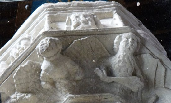 Northleach, UK: Angels holding up the font and trampling the devil underfoot