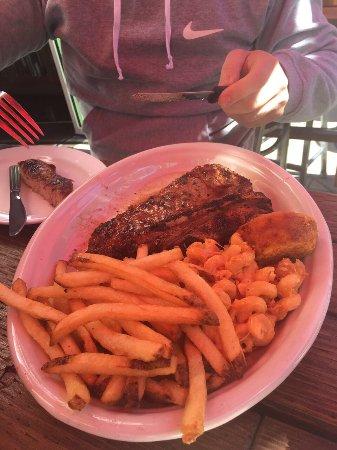 T bone com uma massa e fritas. Os pratos são bem servidos. Serve umas duas pessoas.