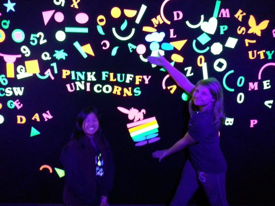 Town and Country, MO: Girls having fun creating their own saying on the blacklight wall.