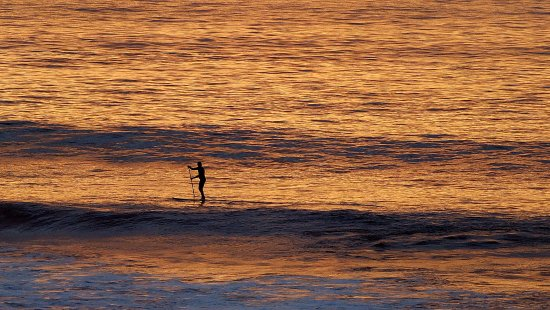 Prevelly, Αυστραλία: A lone paddle boarder rides the golden swells ...