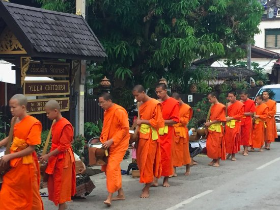 Monks collecting alms outside in front of Villa Chitdara
