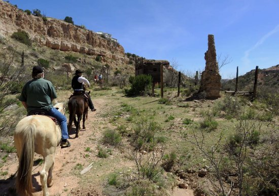 Riding past old cabin ruins in the canyon.