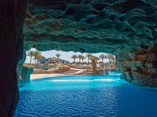 The swimming pool features a cave with a waterfall - Picture ...