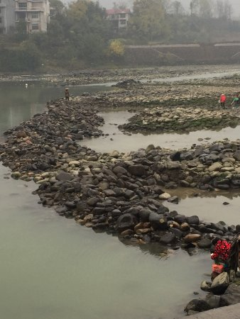 Xiushan County, China: locals gathering stones and fish