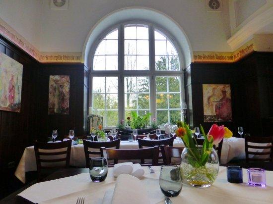Annweiler am Trifels, Tyskland: Das Restaurant im Kurhaus Trifels im April 2017. Angenehme Atmosphäre, Tulpensträuße auf den Tis