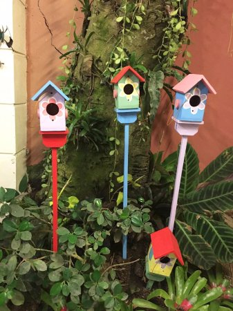 Little Bird Houses Decorating A Dining Area On The Garden Ground