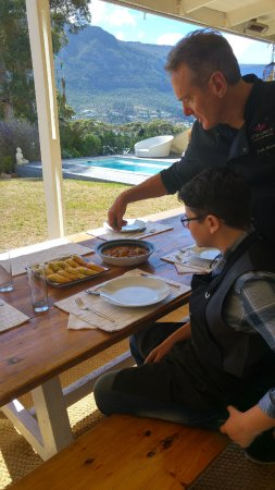 Hout Bay, Sudáfrica: Chef Brett show Michaella how to garnish her dish when serving.