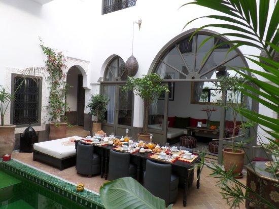 Table du petit-déjeuner à côté du bassin et du salon ...