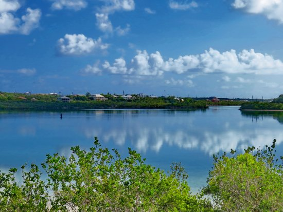 Harbour Club Villas & Marina: Lone fisherman in a calm Flamingo Lake with cloud reflections in the waters