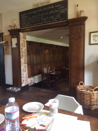 Wrotham Heath, UK: Log-fire to the right, more tables through the arch
