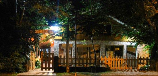 Hotel Orongo: Foto noturna da entrada do hotel. No detalhe a loja de artesanato.