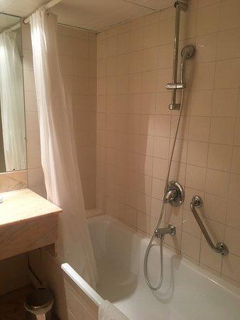 Le Yachtman : Salle de bain vieillotte avec rideaux de douche tout sauf hygiénique, chambre sans charme