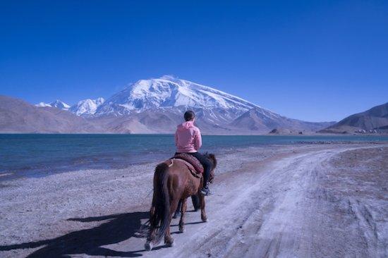 Kashi, China: Horse riding at Karakul lake in the shadow of Muztagh Ata