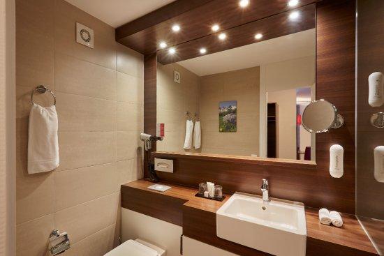 Moderne Badezimmer mit Duscheoder Badewanne im H+ Hotel & Spa ...