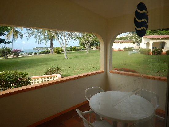 view from inside glass sliding door looking out to front porch and