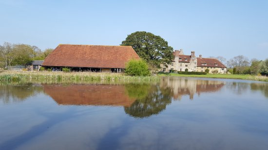 Arlington, UK : The barn and main priory house from across the moat